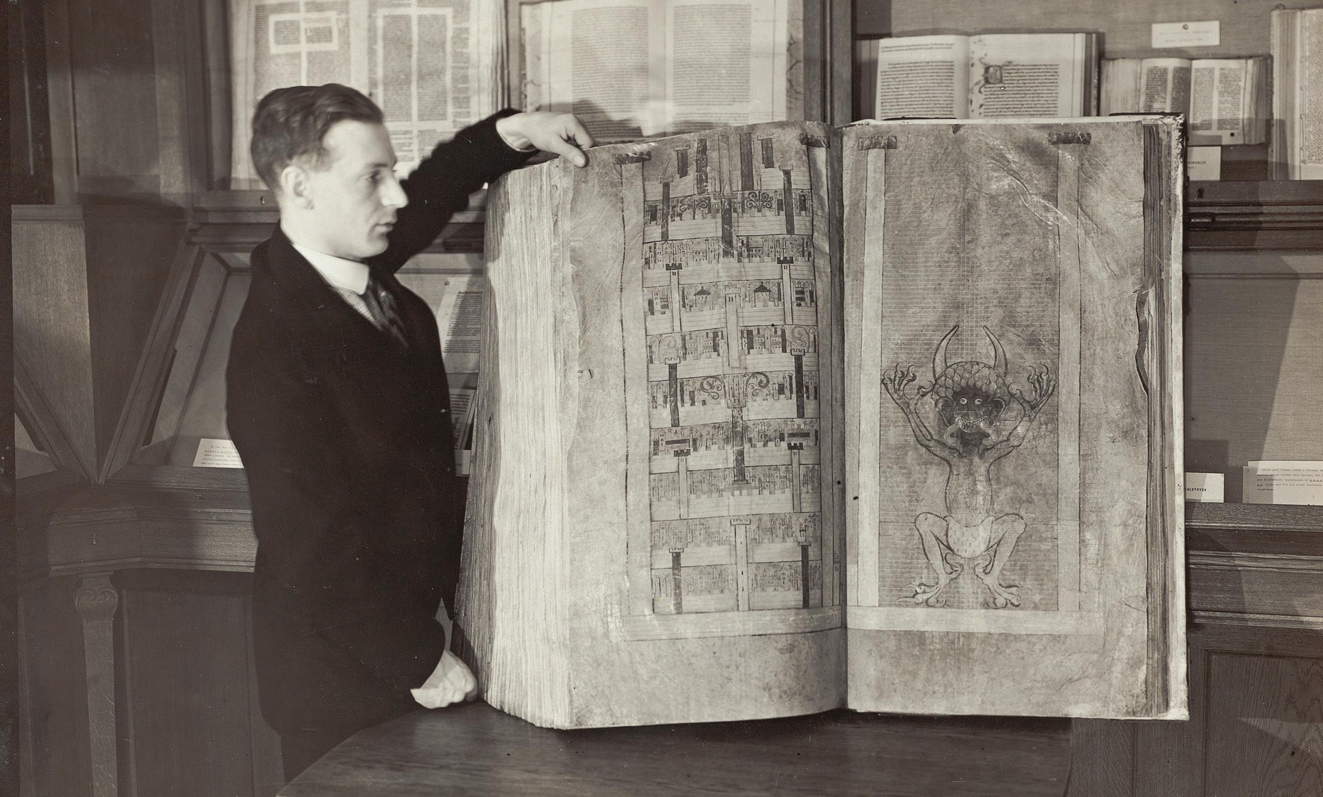 A black and white photo of a man showing a giant book.