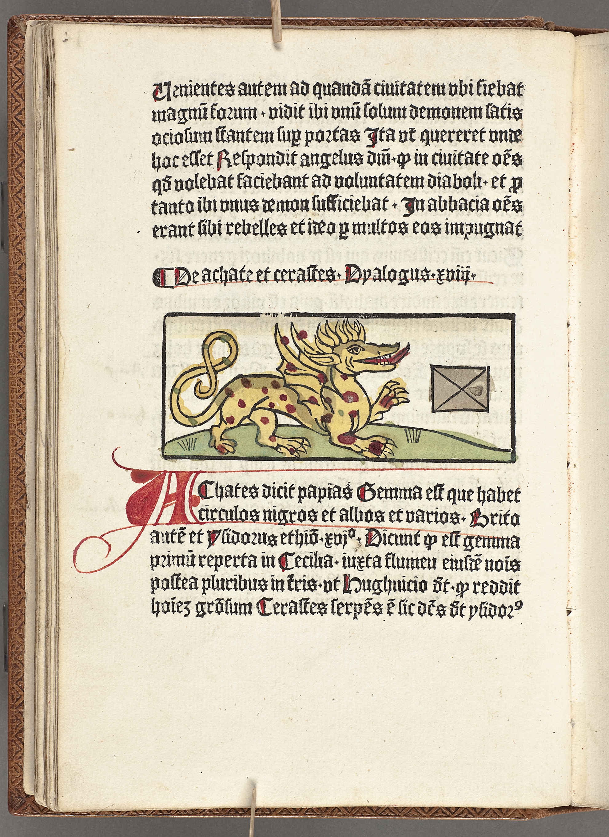 Old book page with gothic writing. In the middle is a dragon with his tongue outside his mouth.