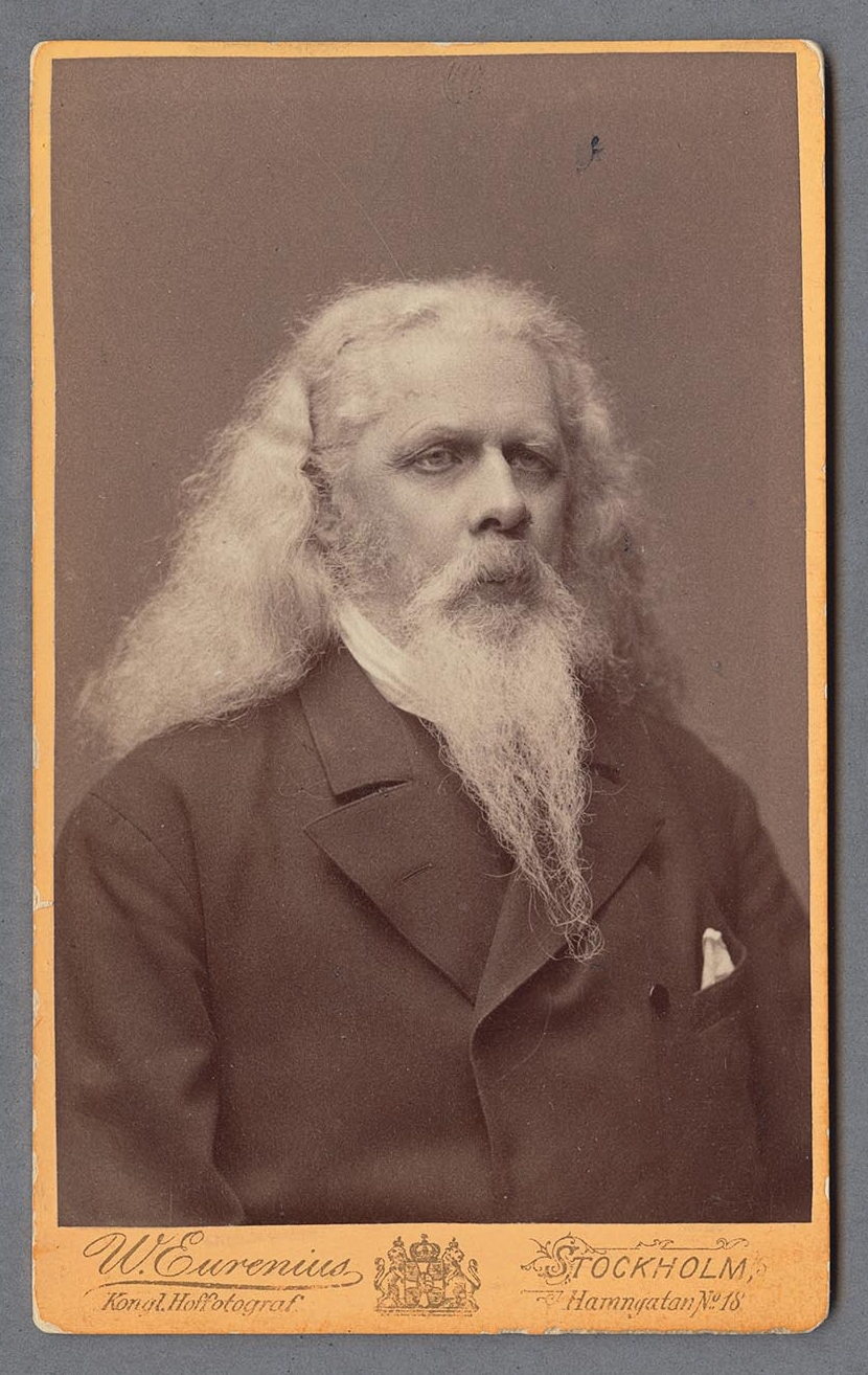 Black and white portrait of man with long white hair and beard.