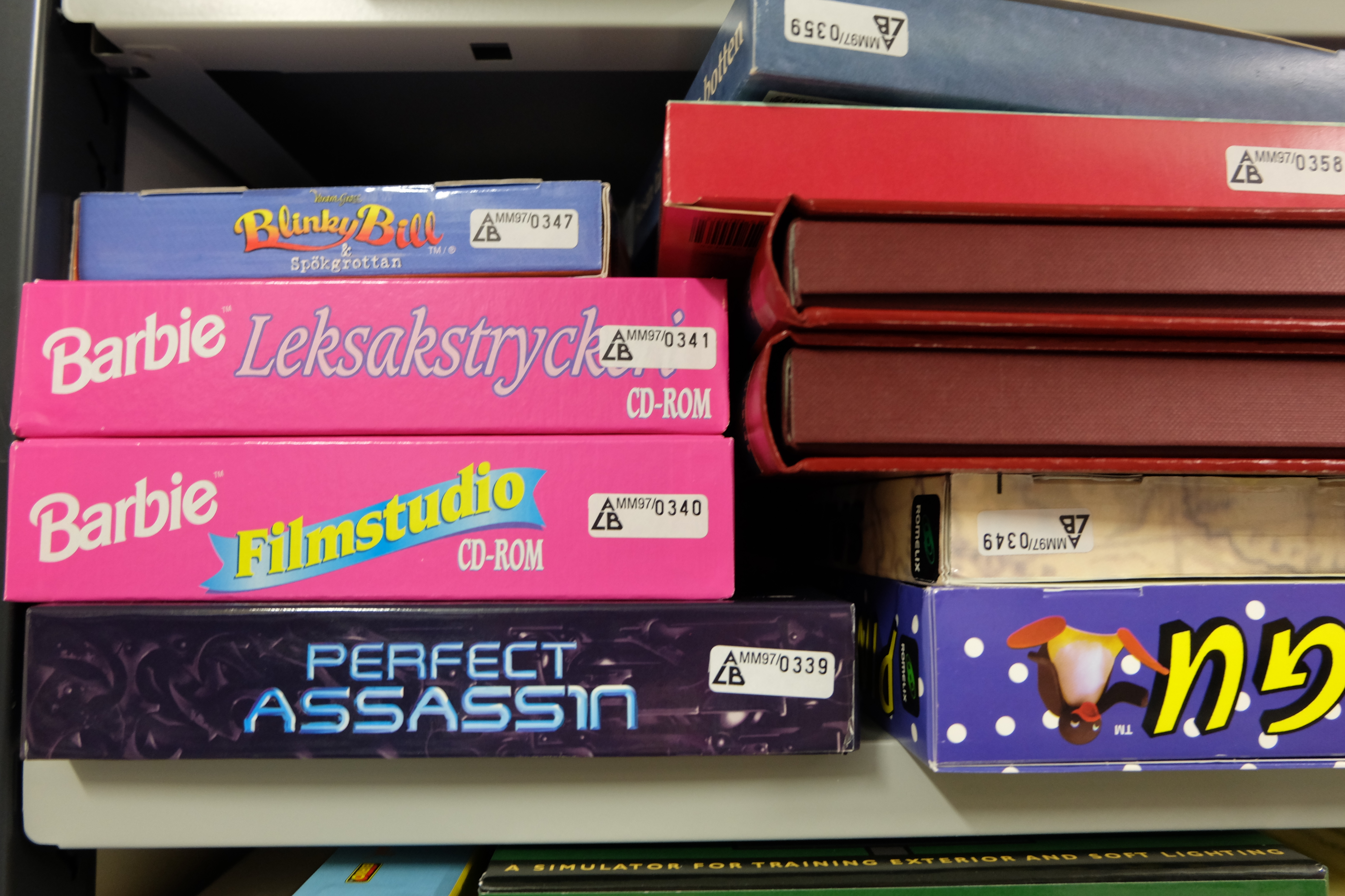 "Shelf with computer games. At the front are some pink covers with the text ""Barbie""."