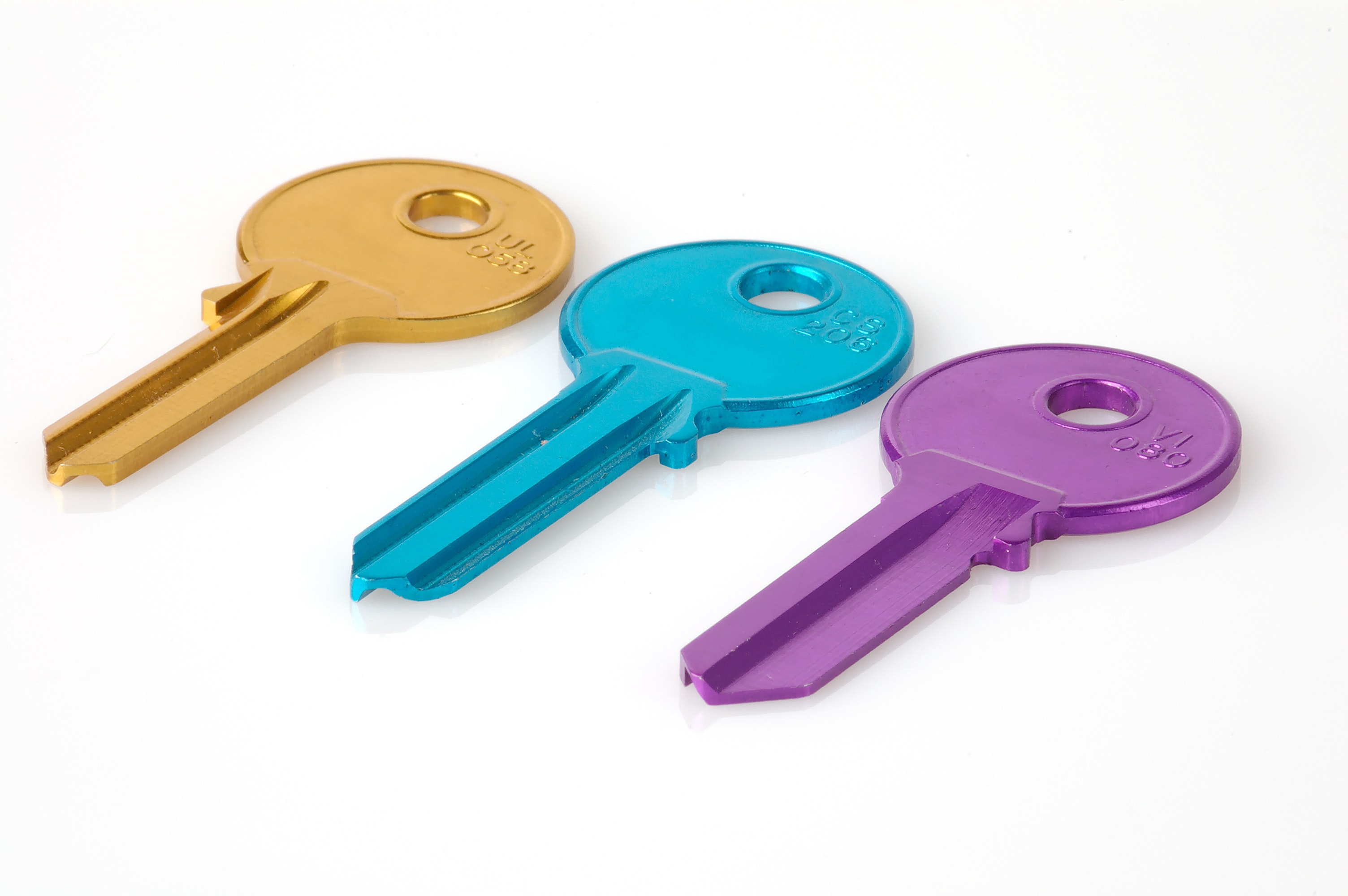 Three keys, yellow, blue and purple, on a white surface.