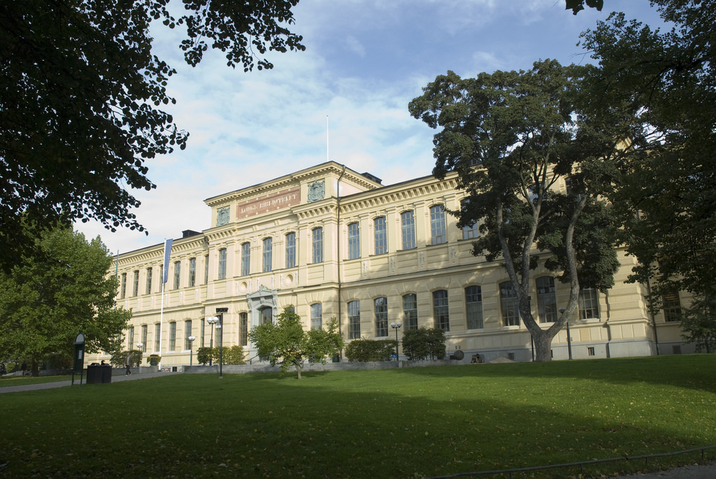 A picture of the National library in the park Humlegården. The building is yellow.