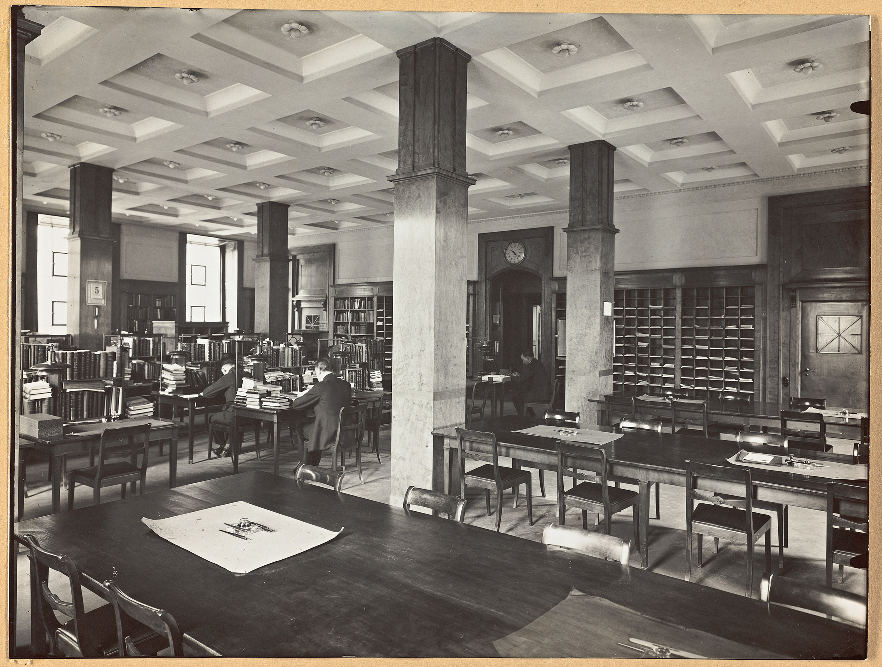 Large hall with four pillars, bookshelves, two large tables with several chairs around and individual reading areas.